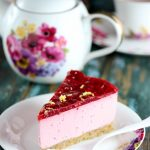 My PCOS Kitchen - Low Carb No Bake Raspberry Lemon Cheesecake (Gluten-free & Sugar-free) - A slice of cheesecake cut over a flower plate with a white fork. Beautiful flower tea kettle behind cheesecake.