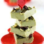 Low Carb Paleo Green Tea Matcha Fudge - My PCOS Kitchen - Green tea fat bombs stacked over one another over a red heart Valentine's Day plate.