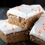 Sugar Free Carrot Cake - My PCOS Kitchen - Square carrot cake bars piled on top of another with some sugar free cream cheese frosting.
