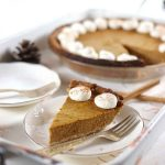 A slice of sugar free pumpkin pie on a white metal tray with a round pumpkin pie in the background.
