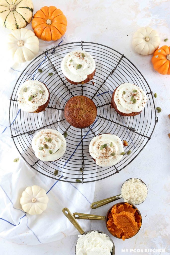 An overhead photography of pumpkin cupcakes with cream cheese frosting on a french vintage cooling rack.